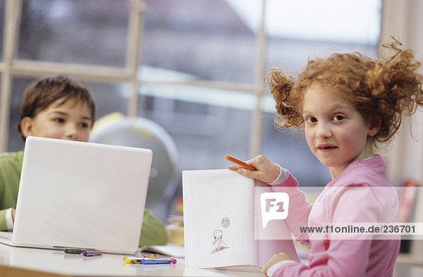 Boy using laptop  girl (7-9) drawing