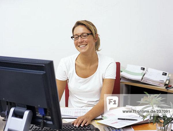 weibliche Büroangestellter auf ihrem Schreibtisch  lächelnd auf gute Nachricht