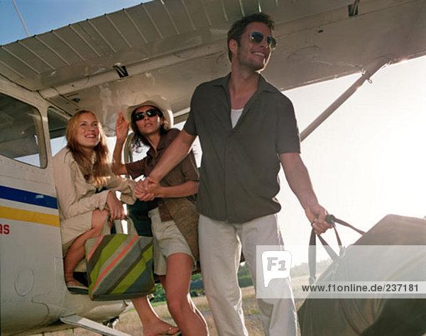 ein Mann und zwei Frauen posiert wie Fashion-Modelle in der Nähe von kleinen Propellermaschine
