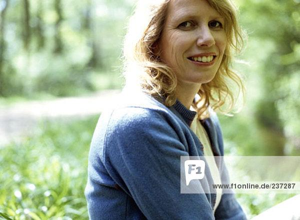 Portrait einer Frau in Wäldern in die Kamera lächelnd Außenaufnahme