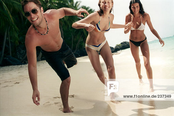 two women and one man having fun on tropical beach