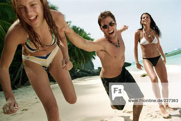 zwei Frauen und ein Mann posiert auf tropischen Strand
