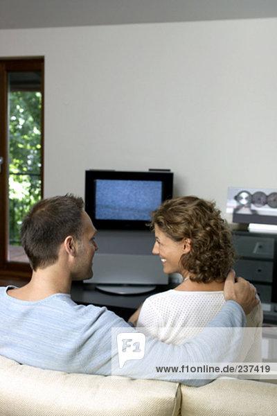 Paar auf Sofa an Fernseher sitzen