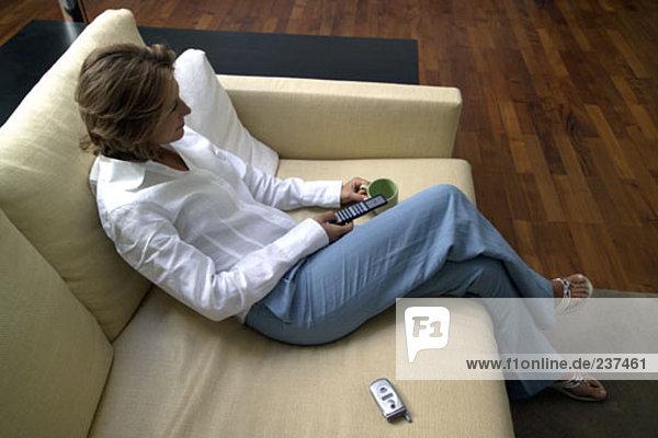 erhöhte Ansicht Frau sitzt auf Sofa mit Fernbedienung  Fernsehen