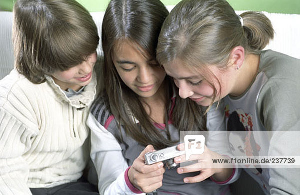 three children looking at display of digital camera