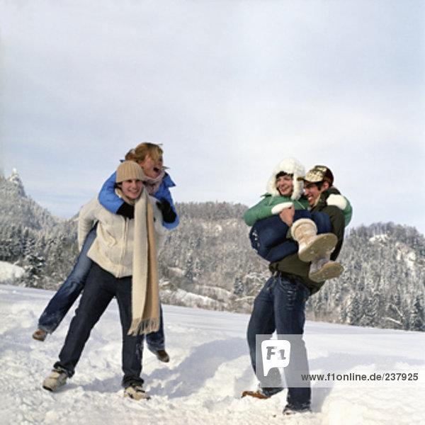 zwei Teenager Paare tun piggyback Rides im Schnee