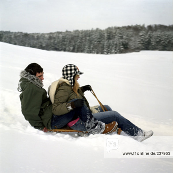 a teenage couple sledging in the snow