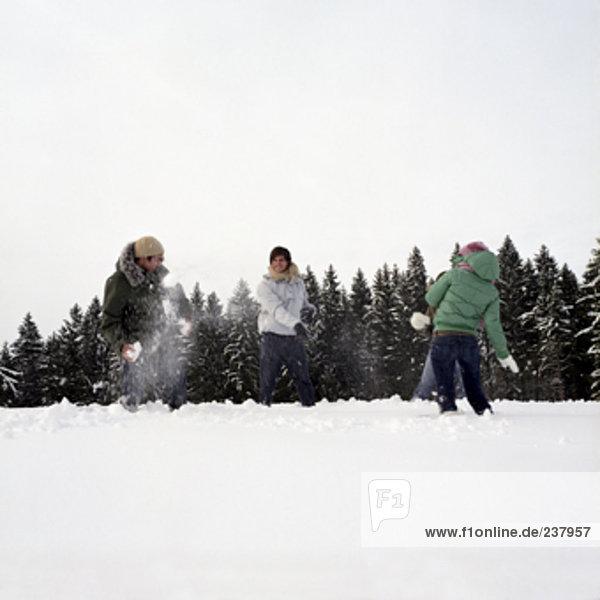 vier Jugendliche haben ein Schneeball kämpfen im Schnee