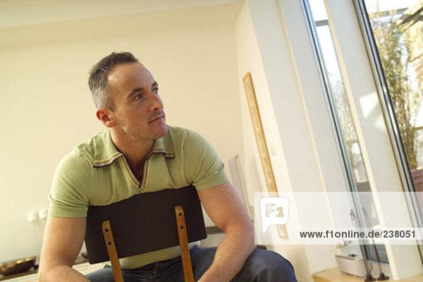 junger Mann auf Stuhl sitzen und Blick aus Fenster