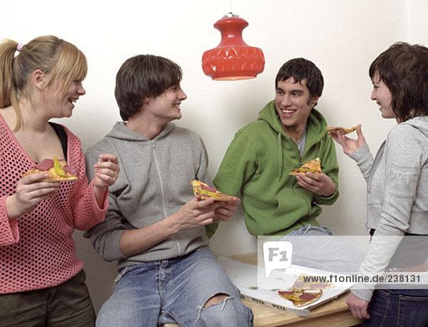 Jugendliche teilen eine Pizza zum Mitnehmen