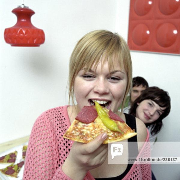 blonde Teenager beißen in Stück pizza