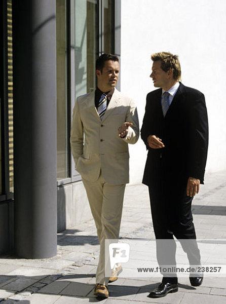 zwei Geschäftsleute haben ein Gespräch beim gehen zusammen