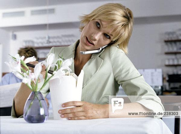 Frau isst mit Stäbchen beim sprechen auf mobile