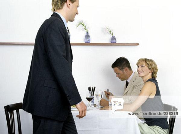Geschäftsleute mit Mittagessen im Restaurant  Frau Blick auf Mann vorbei