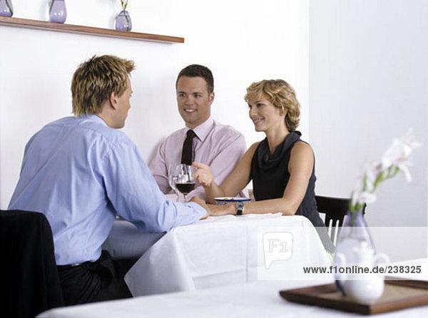 drei Geschäftsleute sitzen in einem restaurant