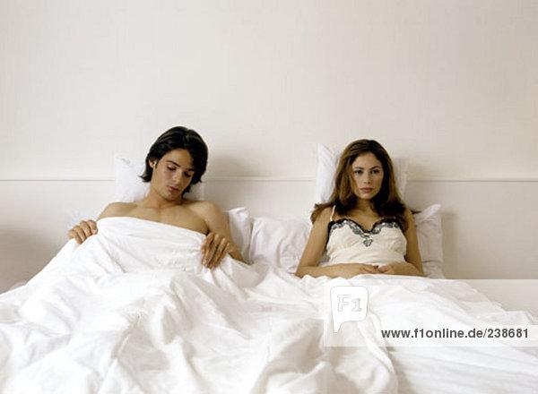 Paar im Bett liegend  sieht Frau Blick desinteressiert Mann aus dem Nähkästchen
