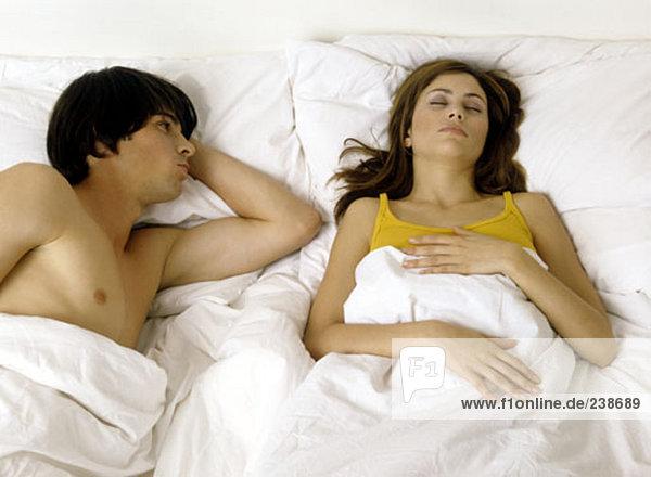 Paar im Bett  jungen Mann gerade schlafende Frau