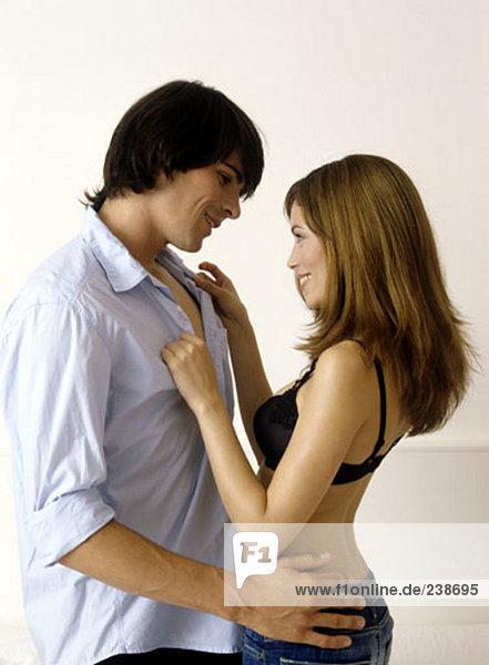 junges paar im Bett  Frau unbuttoning Shirt des Menschen von Angesicht zu Angesicht