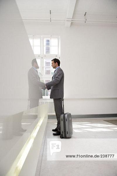 Kaufmann mit Silber Koffer Gepäck warten an Rezeption in lobby