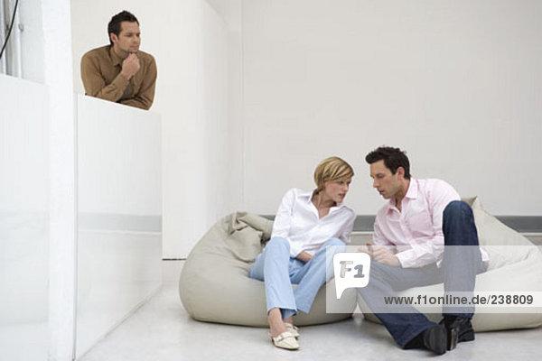 Mann und Frau Flüstern zueinander  wie ein anderer Mann Uhren und hört