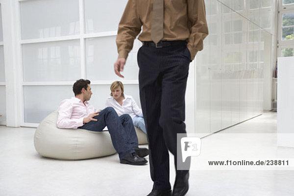 Mann und Frau in Office zu erstellen  während Man im Vordergrund die Übergabe ist sprechen