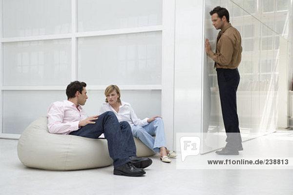 Mann anhören Gespräch zwischen zwei klatschen Geschäftsleuten in office