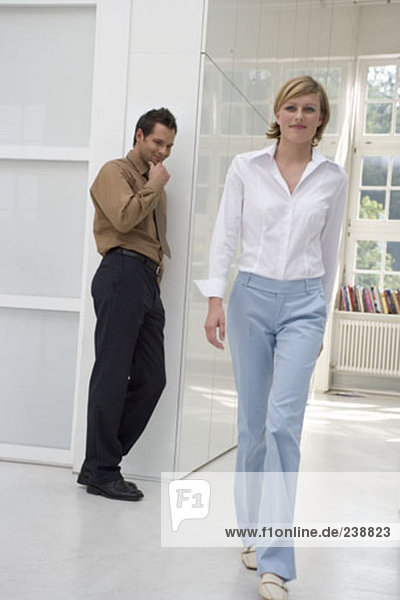young grinning man looking at rear of female colleague passing by in office building