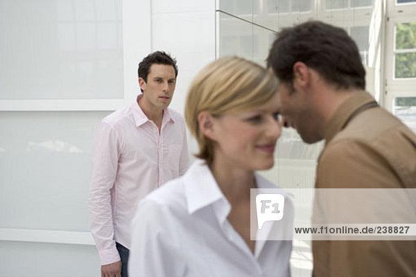 Büroangestellte Flüstern zueinander  unbehaglichen schauenden Mann im Hintergrund hören