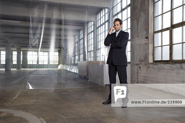 junge Immobilienmakler in leere Gebäude und sprechen auf seinem Handy stehend