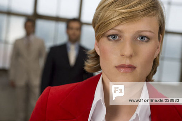portrait of serious looking businesswoman  two men standing in background