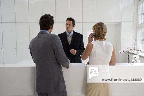 während Frau auf ihrem Mobiltelefon spricht im Gespräch mit Geschäftsmann an Rezeption Rezeptionist