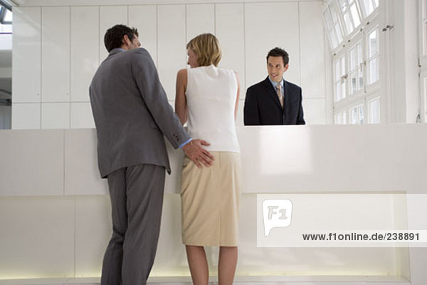 young couple waiting at reception desk in lobby  man touching woman´s behind