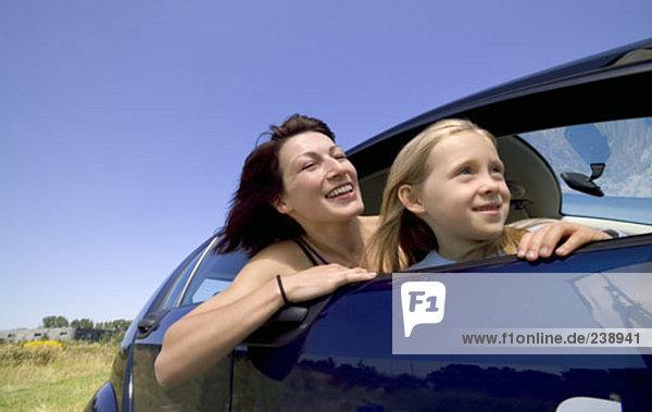 Mutter und Tochter von Autofenster gelehnt