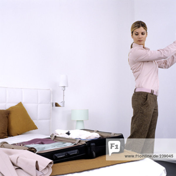 geschäftsfrau Verpackung ihr Gepäck im Hotelzimmer