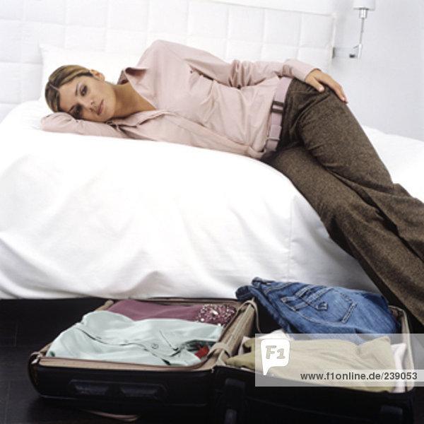 ernste schauende Frau liegen auf dem Bett  packte Koffer neben ihr