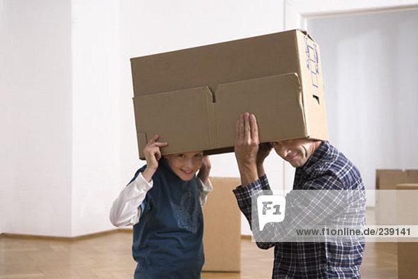 Menschlicher Vater Sohn unterhalb verpacken Umzug umziehen ausziehen einziehen Pappe