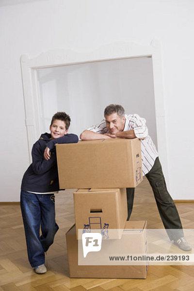 Portrait Pose Menschlicher Vater Sohn Bewegung Eigentumswohnung Pappschachtel Pappkarton Pappe neues Zuhause