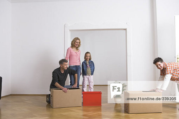 family packing moving boxes  while moving home