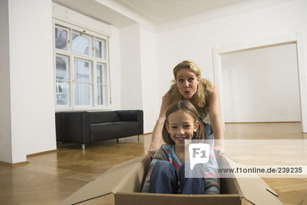 mother and daughter having fun with cardboard boxes moving into new home