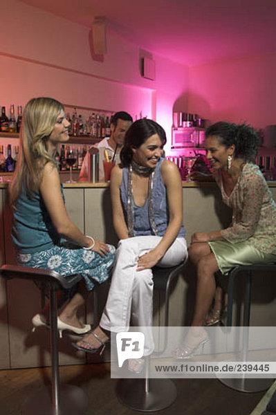 drei junge Frauen Teilen einen Lachen in der Bar in einer Nacht heraus