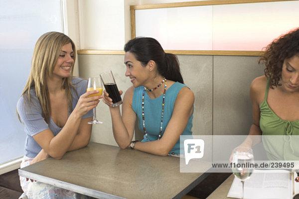 zwei Freundinnen Toasten zueinander im cafe