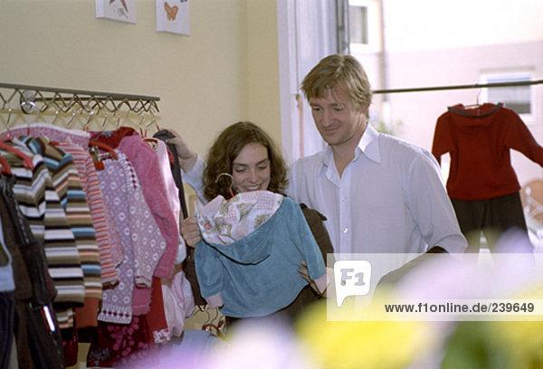junges paar shopping für neue Baby-Kleidung