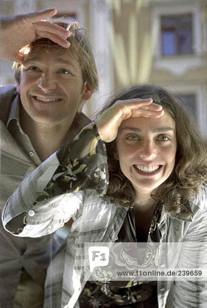 glückliches junges Paar gucken durch Schaufenster