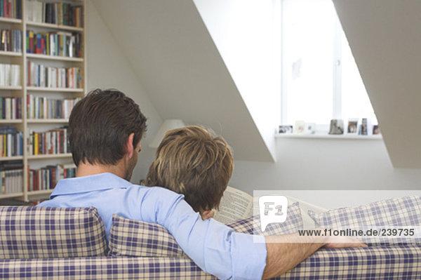 sitzend  Interior  zu Hause  Buch  teilen  Rückansicht  Ansicht  Couch  Taschenbuch