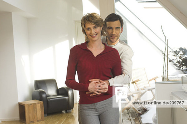 portrait of mature couple standing together in their living room at home