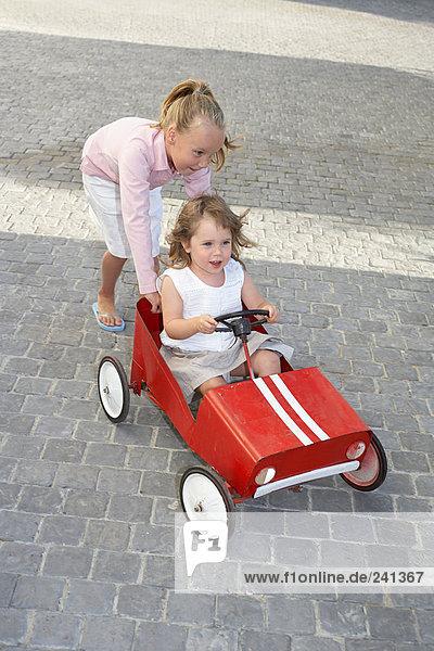 Schwester  die ihre jüngere Schwester in einem Spielzeugauto schubst.