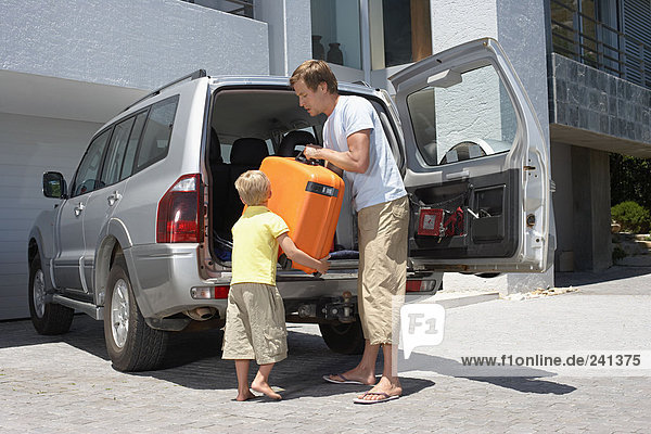 Sohn hilft seinem Vater beim Einpacken des Autos
