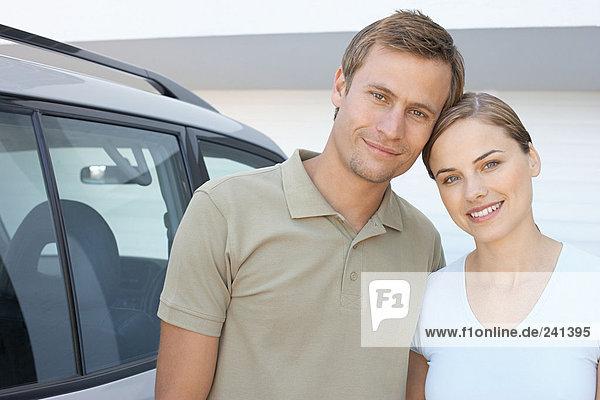 Mittleres erwachsenes Paar stand draußen mit Auto