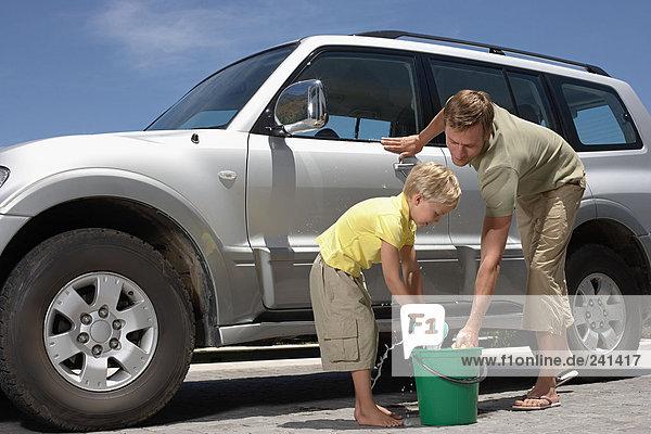 Vater und Sohn waschen Familienauto