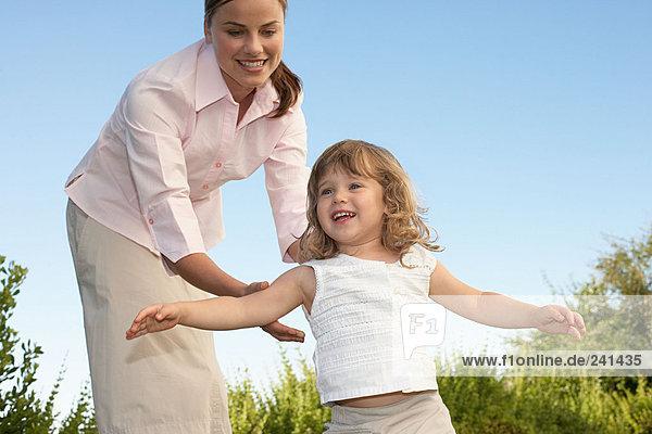 Mutter und Tochter beim Spielen im Garten
